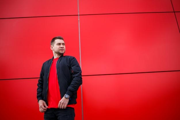 Fajny młody mężczyzna w modnych okularach przeciwsłonecznych w stylowej czerwonej koszulce i czarnej kurtce stoi w pobliżu czerwonego budynku w mieście. atrakcyjny nowoczesny facet. modna letnia odzież męska. styl uliczny