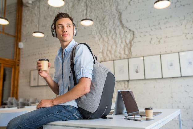 Fajny młody przystojny mężczyzna siedzi na stole w słuchawkach z plecakiem w biurze współpracującym pije kawę
