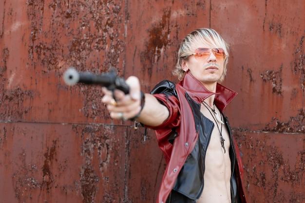 Fajny, nowoczesny młody mężczyzna z nagim torsem w modnej czarno-czerwonej skórzanej kurtce z modnymi okularami przeciwsłonecznymi wystrzeliwuje z broni vintage w pobliżu starego zardzewiałego budynku.