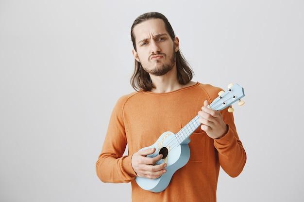 Fajny przystojny facet grający na ukulele