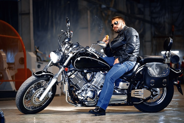 Fajny rowerzysta brodaty mężczyzna w okularach przeciwsłonecznych, siedząc na motocyklu i paląc cygaro