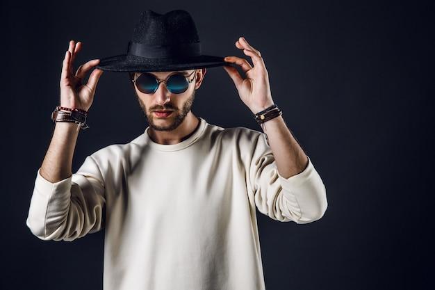 Fajny stylowy przystojny mężczyzna w okularach przeciwsłonecznych, trzymając kapelusz