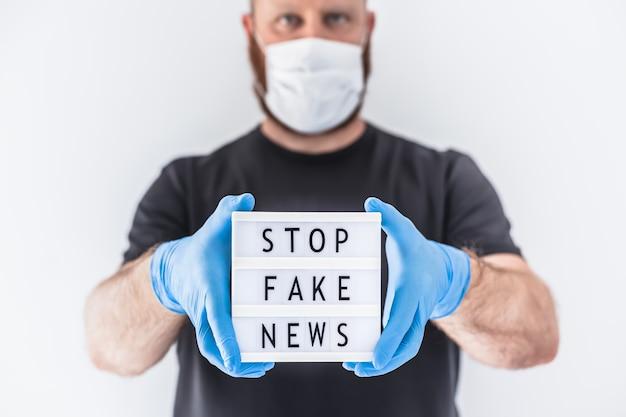 Fake news infodemics podczas koncepcji pandemii covid-19. mężczyzna w masce ochronnej i rękawiczkach medycznych na rękach trzymających lightbox z tekstem zatrzymaj fałszywe wiadomości. ludzie chcą poznać prawdę o koronawirusie