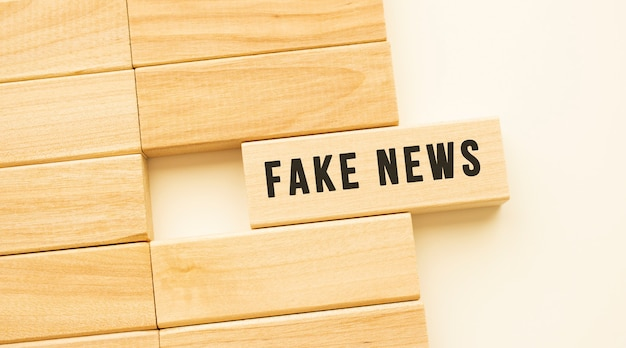 Fake news tekst na drewnianym pasku leżącym na białym stole. pojęcie.