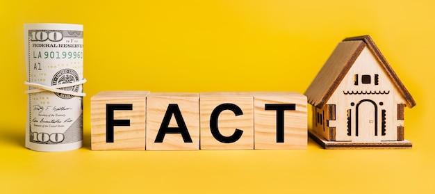 Fakt z miniaturowym modelem domu i pieniędzmi na żółtym tle. pojęcie biznesu, finansów, kredytu, podatków, nieruchomości, domu, mieszkania