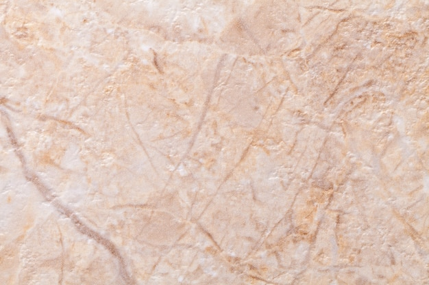 Faktura dekoracyjnego tynku w kolorze beżowym imitującym stary łuszczący się mur. przestarzałe kremowe i brązowe pęknięte tło, zbliżenie.
