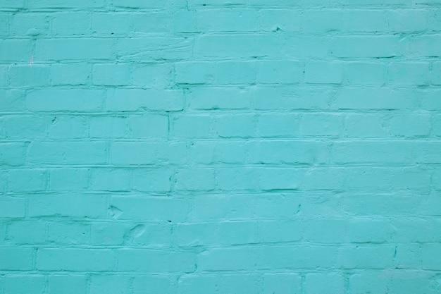Faktura elewacji budynku ceglanego muru z rzędów cegieł pomalowanych na kolor turkusowy