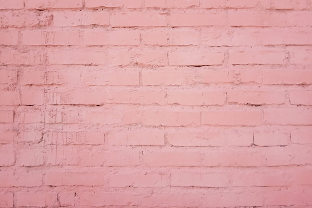 Faktura elewacji budynku ceglanego muru z rzędów cegieł pomalowanych na różowo