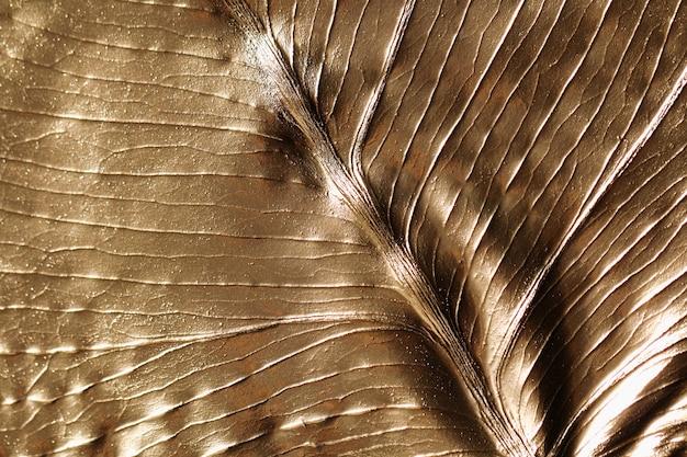 Faktura liścia monstery pomalowana na złoty kolor. abstrakcyjne tło.