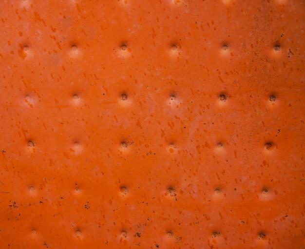 Faktura metalu pomalowana na kolor pomarańczowy. szorstka i popękana powierzchnia.