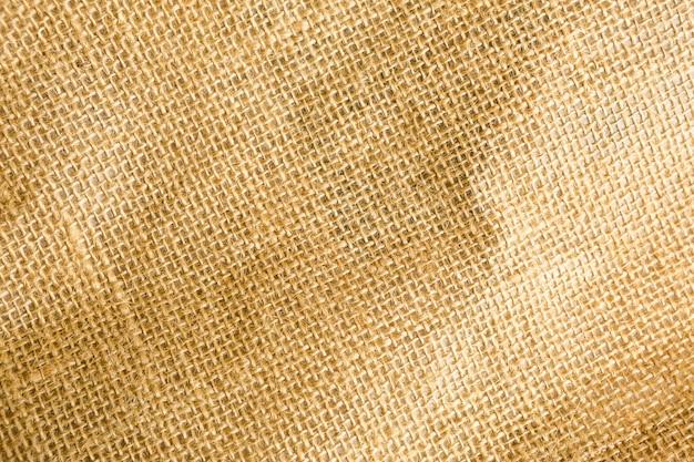 Faktura płótna, szorstki splot w klatce z naturalnego włókna, kolor żółto-brązowy. copyspace, zbliżenie