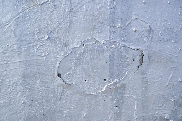 Faktura ściany z wytartym starym tynkiem, pomalowana na kolor srebrny