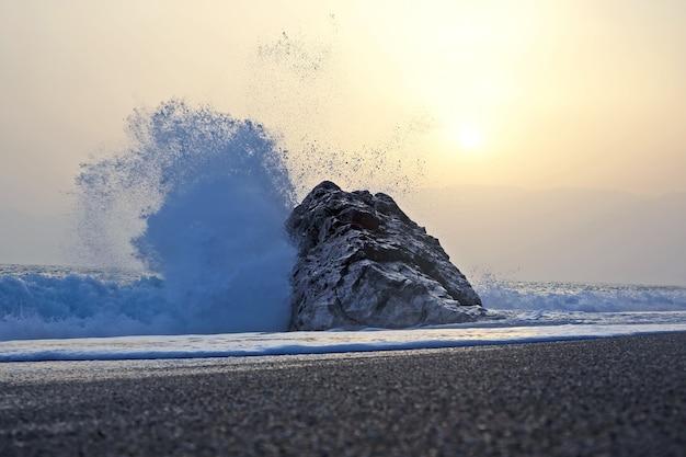 Fala morska bije o skałę przed zachodem słońca