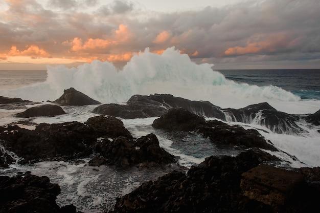 Fala morska o wysokiej pianie i wiele skał pod zachmurzonym niebem podczas zachodu słońca w letni wieczór
