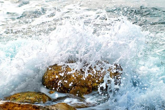 Fala morska pokryła skałę. rozpryski i krople wody