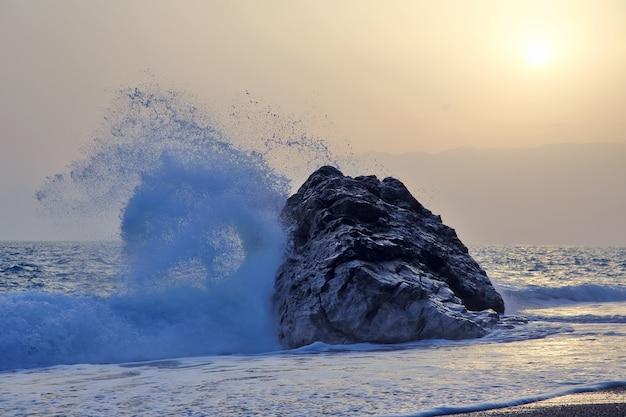 Fala morska uderzająca z siłą w skałę o zachodzie słońca