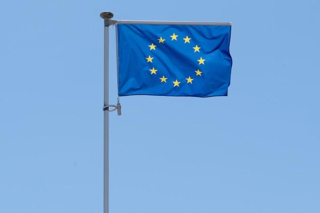 Fala niebieska flaga unii europejskiej ue w błękitne letnie niebo w macie