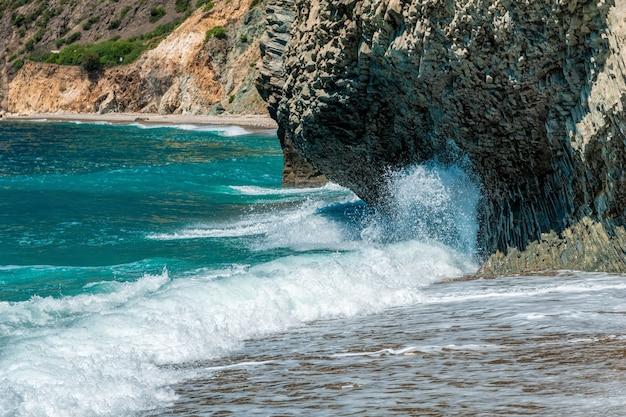 Fala oceaniczna uderzająca w bazaltowe skały przybrzeżne, jak na islandii. spray morski. lazurowa woda.