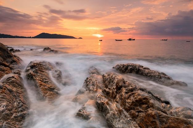 Fala ruchu przez skały o zachodzie słońca z niebem o zmierzchu. piękny andamański krajobraz na plaży kalim patong w phuket, tajlandia. słynny cel podróży na letnie wakacje.