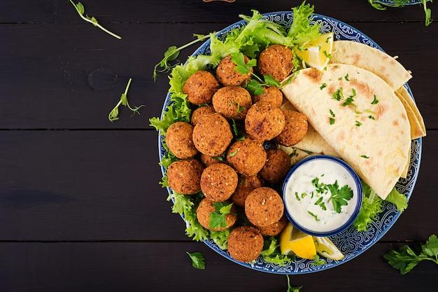 Falafel, hummus i pita. bliskowschodnie lub arabskie potrawy na ciemnym stole jedzenie halal. widok z góry. skopiuj miejsce