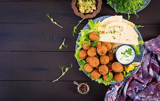 Falafel, hummus i pita. bliskowschodnie lub arabskie potrawy na ciemnym tle. jedzenie halal. widok z góry. skopiuj miejsce