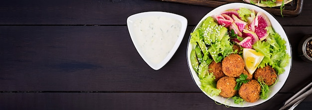 Falafel i świeże warzywa. miska buddy. dania z bliskiego wschodu lub arabskie widok z góry. transparent