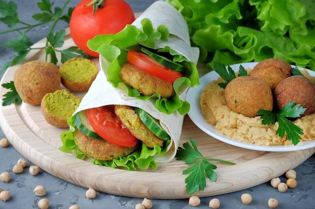 Falafel i warzywa zawinięte w lawasz i miskę z hummusem na desce do krojenia.