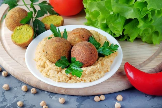 Falafel kulki i miska z hummusem na desce do krojenia. zdrowe jedzenie wegetariańskie i wegańskie.