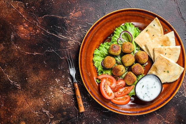 Falafel wegetariański z pitą, świeżymi warzywami i sosem na talerzu. ciemne tło. widok z góry. skopiuj miejsce.