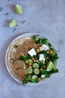 Falafel z sałatką, hummusem i chlebem naan. widok z góry na szary