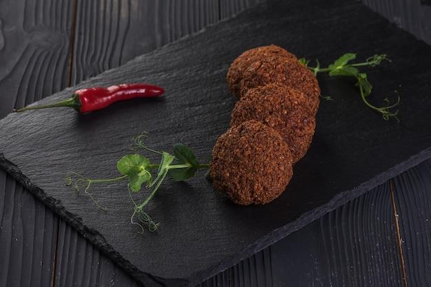 Falafel z sosem czosnkowym na czarnej kamiennej tacy. jedzenie wegańskie