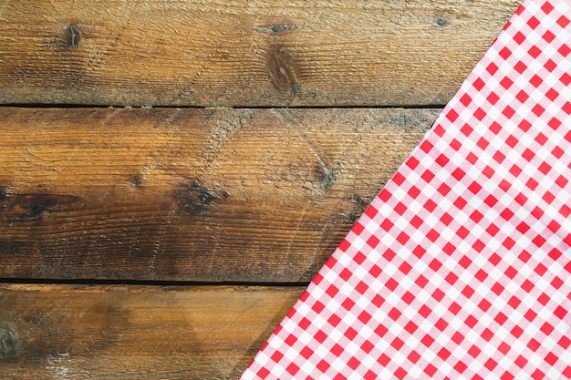Fałdowa czerwona w kratkę pielucha na drewnianym stole