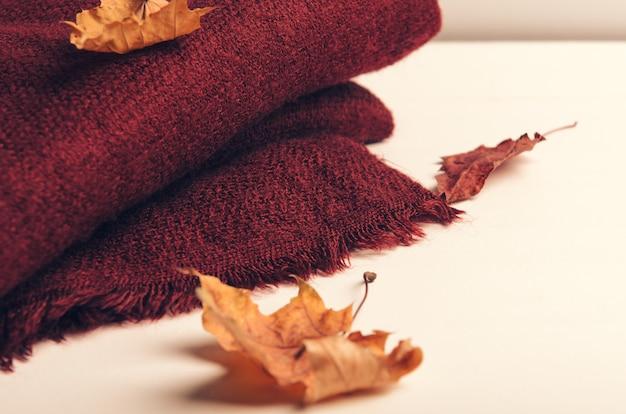 Fałdowy burgundowy szalik na białym tle z jesień liśćmi