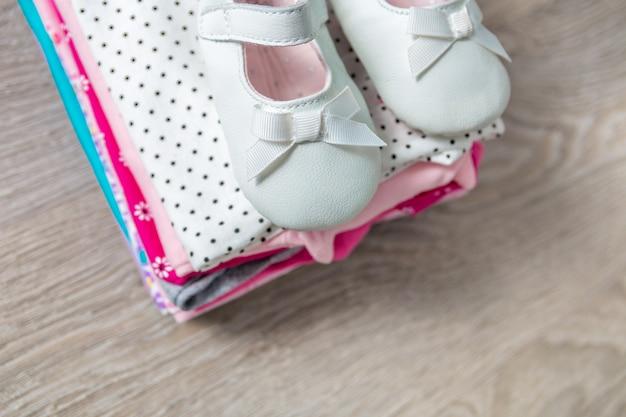 Fałdowy różowy i biały body z butami na nim na szarym drewnianym tle. pieluszka dla noworodka. stos ubrań dla niemowląt. strój dziecięcy. skopiuj miejsce