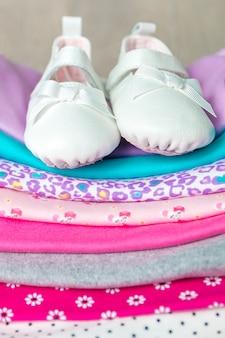 Fałdowy różowy i biały body z butami na nim na szarym drewnianym tle.