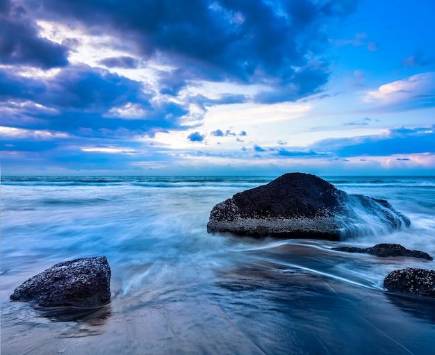 Fale i skały na plaży o zachodzie słońca