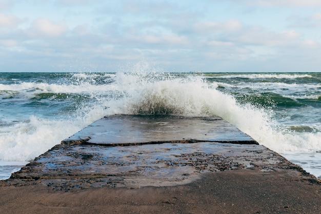 Fale łamiące się na betonowym molo przy wietrznej pogodzie