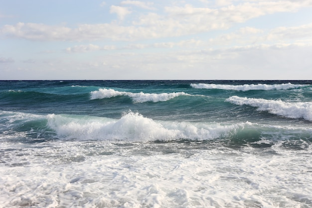 Fale morskie na powierzchni wody morskiej podczas silnych wiatrów i złej pogody, słoneczny dzień, niebo z chmurami.