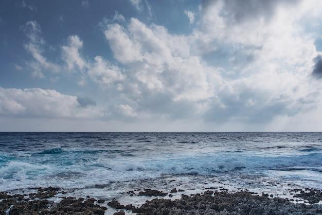 Fale morskie rozbijają się o nierówny skalisty brzeg