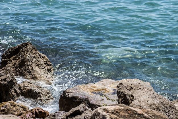 Fale morskie rozbijające się o skały na dzikiej kamienistej plaży.
