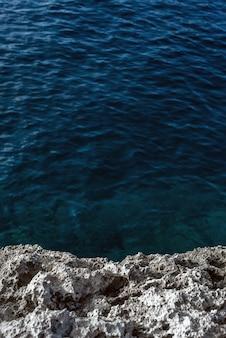 Fale morskie zacierają się na skały na plaży