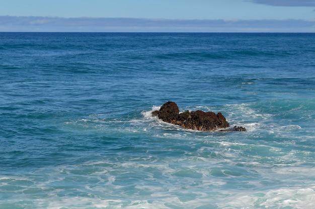 Fale na czarnej skale pośrodku morza