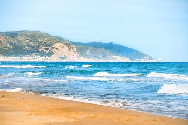 Fale na długiej, morskiej plaży z piaskiem i błękitną wodą