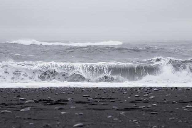 Fale na pięknej wulkanicznej plaży z czarnym piaskiem na islandii.