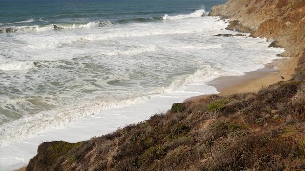 Fale oceanu i skały, monterey, północna kalifornia, usa. 17-kilometrowa przejażdżka w pobliżu big sur, nadmorskiego kurortu golfowego przy autostradzie pacific coast highway. rozpryskująca się woda i morska bryza żwirowej plaży. podróż samochodem.