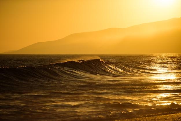 Fale oceanu lub morza. tropikalna plaża, tło podróży wakacje. zachód słońca krajobraz. krajobraz wschód słońca.