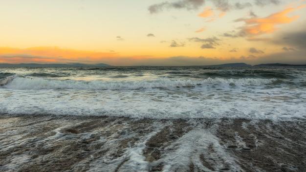 Fale oceanu rozbijające się na brzegu podczas zachodu słońca