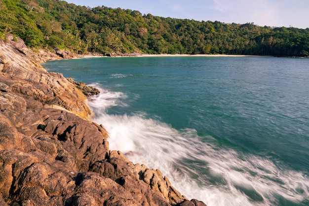 Fale oceanu rozbijające się na skalistym brzegu, fala morska rozbija się na rozpryski i białą pianę na plaży w phuket tajlandia piękny widok na krajobraz morski.