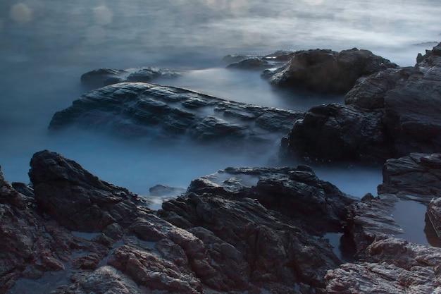 Fale oceanu upaść na skałach w zachodzie słońca