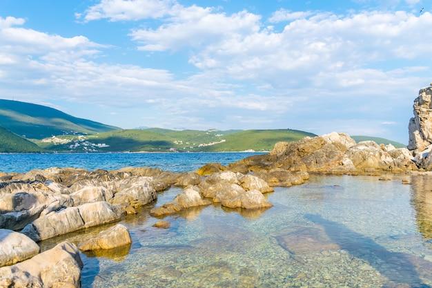 Fale rozbijają się o przybrzeżne kamienie w adriatyku w czarnogórze, w zatoce boka-kotor